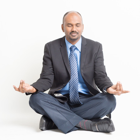 Business stress management concept. Full length Indian businessman in formal suit eyes closed sitting in meditation yoga pose, on plain background.