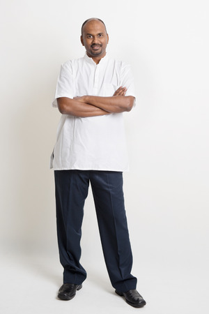 business casual: Full body casual mature Indian business people arms crossed standing on plain background. Stock Photo