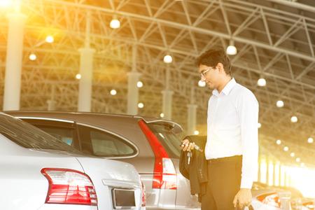 parking lot interior: Indian business man at car park, holding car remote key.