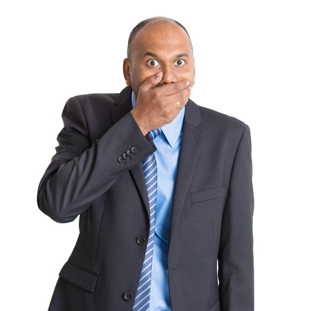 stunned: Portrait of shocked mature Indian businessman covered mouth, standing on plain background with shadow. Stock Photo