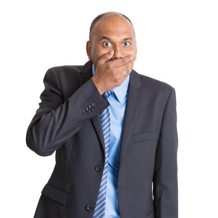 Retrato de hombre de negocios indio sorprendido madura cubierto la boca, de pie en el fondo plano con la sombra. Foto de archivo - 47875403