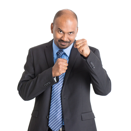 fist fight: Mature Indian businessman in kungfu fighting mood, standing on plain background with shadow.