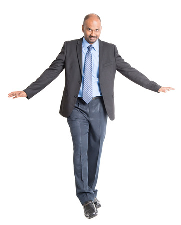 people in action: Full body Indian businessman walking balance , front view on plain background.