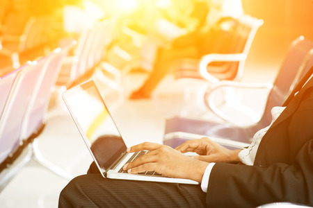 sunlight: Business man using laptop while waiting his flight at airport, beautiful golden sunlight background. Stock Photo