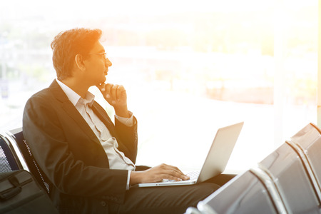 airports: Business man using laptop while waiting his flight at airport, beautiful golden sunset background.