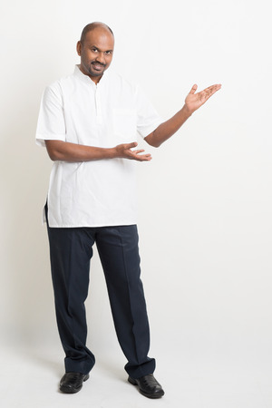 Full length Indian casual man hands showing something on copy space, standing on plain background with shadow. Stock Photo