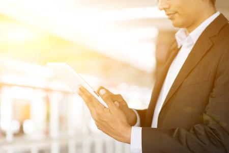 usando computadora: Indian business man using tablet computer while waiting train at railway station, golden sunset background. Foto de archivo