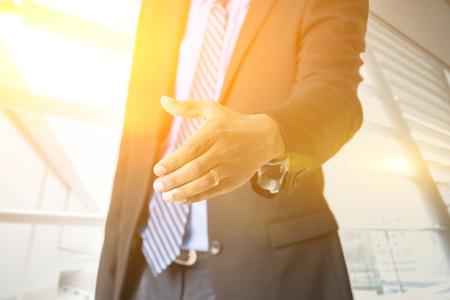 hi back: Close up business people hand offering handshake, golden sunlight from background, sunrise or sunset business.