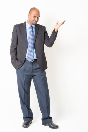 professional people: Portrait of full body mature Indian business man hand showing something, standing on plain background.