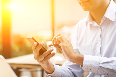 Asian Indian businessman using smartphone at outdoor cafeteria, beautiful blurred golden sunlight at back. Stockfoto