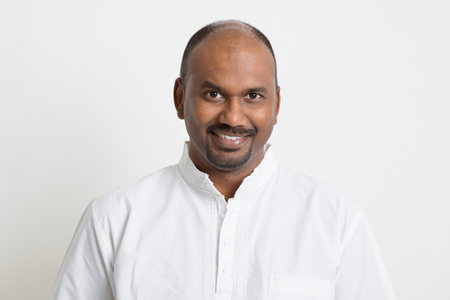 Portrait d'homme mûr Indien d'affaires décontractée souriant, debout sur fond uni avec l'ombre.