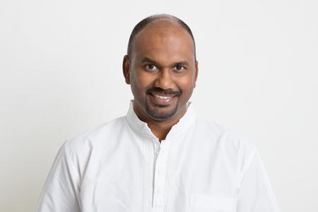 Portret van rijpe toevallige zaken Indiase man glimlachen, staande op duidelijke achtergrond met schaduw.