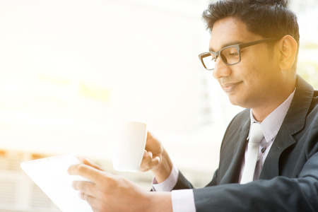 american media: Asian Indian businessman using tablet computer at cafe, relaxing with a cup of coffee. India male business man, modern office building with sunlight as background.