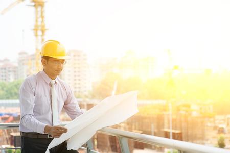 ingeniero civil: India asi�tica ingeniero contratista sitio masculina con casco que sostiene el papel de impresi�n azul inspecci�n en el sitio de construcci�n, gr�a en el fondo.