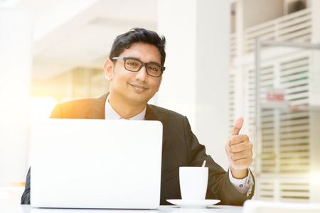 Asian Indian business people using a laptop thumb up at cafe. India male business man, modern building with beautiful golden sunlight as background. Stock Photo