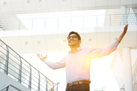 Asian Indian businessman arms outstretched celebrating success, modern office building with morning sunlight as background.