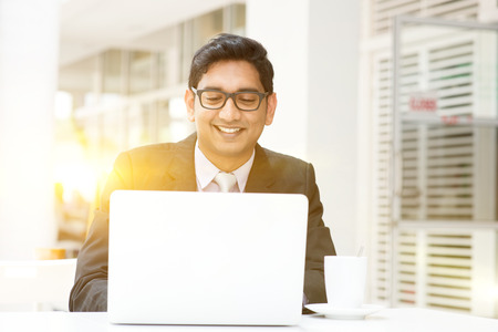 Young Asian Indian business man using a laptop or notebook computer at cafe, with a cup of coffee. India male business man, modern building with beautiful golden sunlight as background. Foto de archivo