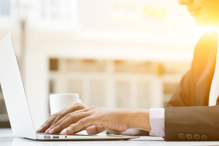 sunlight: Business people using a laptop or notebook computer at cafe, with a cup of coffee. Male business man, modern building with beautiful golden sunlight as background. Stock Photo