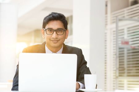successful man: Young Asian Indian business people using a laptop or notebook computer at cafe, with a cup of coffee. India male business man, modern building with beautiful golden sunlight as background. Stock Photo