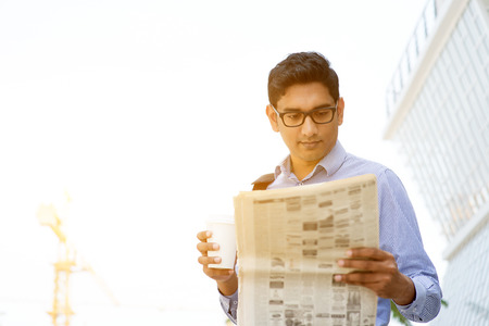 Asian Indian business people holding coffee cup and reading newspaper on the way to work place in morning. Handsome male model.