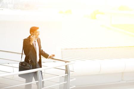 persona llamando: Candid empresario joven asiático indio en el teléfono en el edificio de oficinas al aire libre. India hombre de negocios masculino, la luz del atardecer en el fondo.