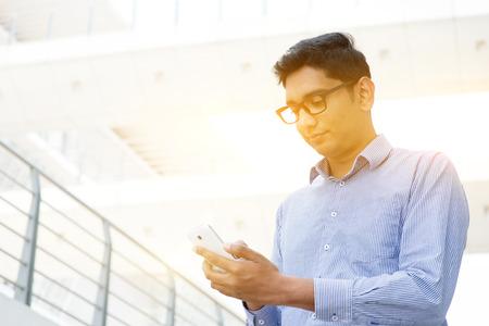 mobile phones: Asian Indian businessman using smartphone, modern urban city sunrise background.