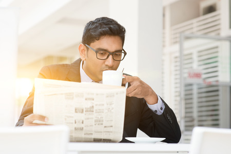Young Asian Indian businessman sipping coffee and reading newspaper at cafe. India male business man, modern office building with beautiful golden sunlight as background.