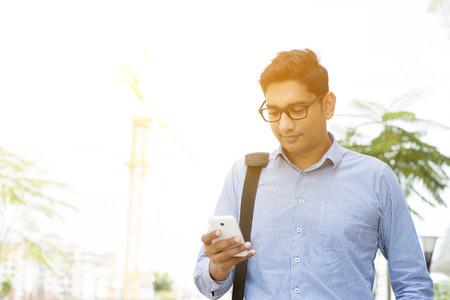 Aziatische Indische bedrijfsmensen texting met smartphone tijdens het lopen naar het kantoor, moderne stedelijke zonsopgang.