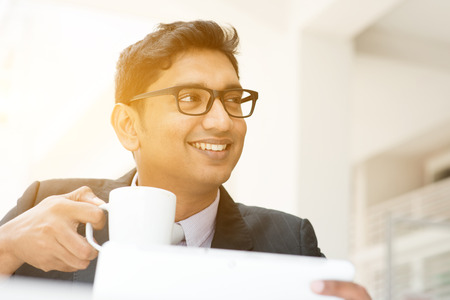 business men: Young Asian Indian businessman using tablet pc at cafe, relaxing with a cup of coffee. India male business man, modern office building with sunlight as background.