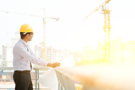 contractor: Asian Indian male site contractor engineer with hard hat holding blue print paper inspecting at construction site, crane with golden sunlight at the background. Stock Photo