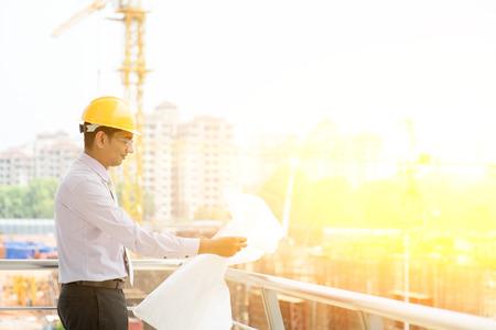 아시아 인도 남성 사이트 계약자 엔지니어 건설 용지, 배경에서 햇빛과 크레인 검사에서 파란색 인쇄 용지를 들고 하드 모자와 함께.