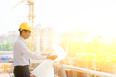 contractors: Asian Indian male site contractor engineer with hard hat holding blue print paper inspecting at construction site, crane with sunlight at the background.