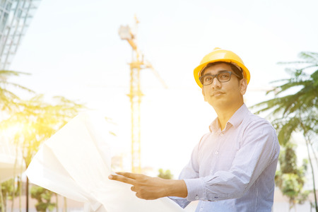 Portrait of a 30s Indian male site contractor engineer with hard hat holding blue print paper at construction site, crane at the background. Stock Photo