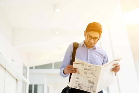 Asian Indian businessman reading newspaper on the way to work in a morning. Handsome male model.