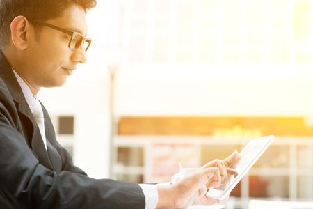 garcon africain: Asiatiques gens d'affaires indiens utilisant tablet pc au café, se détendre avec une tasse de café. Inde homme d'affaires mâle, immeuble de bureaux moderne avec la lumière du soleil en arrière-plan.