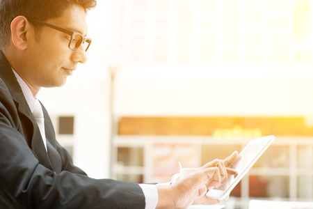 Aziatische Indische mensen uit het bedrijfsleven met behulp van tablet pc in cafe, ontspannen met een kopje koffie. India mannelijke man, modern kantoorgebouw met zonlicht als achtergrond. Stockfoto - 47875322