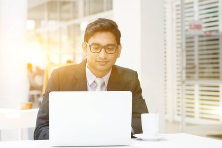smiling businessman: Young Asian Indian businessman using a laptop or notebook computer at cafe, with a cup of coffee. India male business man, modern building with beautiful golden sunlight as background. Stock Photo