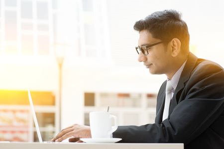 man working computer: Side view of Indian businessman at cafeteria, having a cup of coffee and using internet.