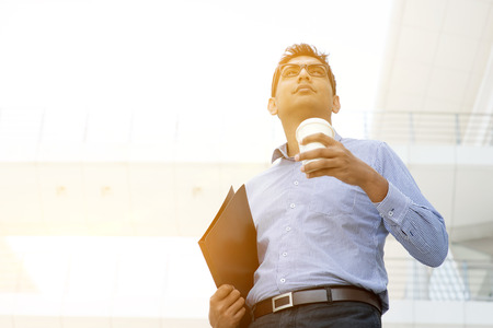 city of sunrise: Asian Indian business man hand holding take away hot coffee cup and file folder in morning sunlight, outdoors modern office business concept.