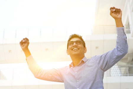 Successful Asian Indian businessman with arms up celebrating his victory, modern office building with morning sunlight as background.