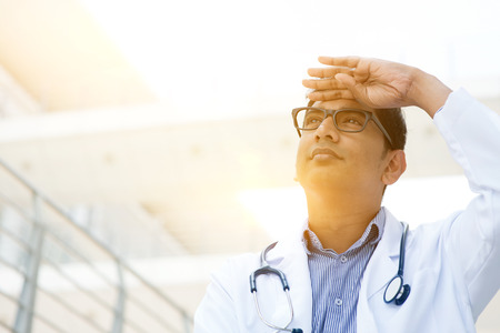 pakistani ethnicity: Portrait of Asian Indian medical doctor hand shielded looking away, standing outside hospital building, beautiful golden sunlight at background.