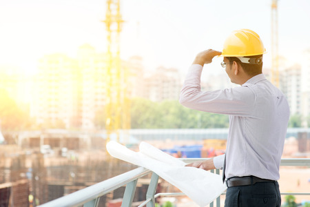 construction project: Asian Indian male site contractor engineer with hard hat holding blue print paper looking away inspecting at construction site, crane with golden sunlight at the background. Stock Photo
