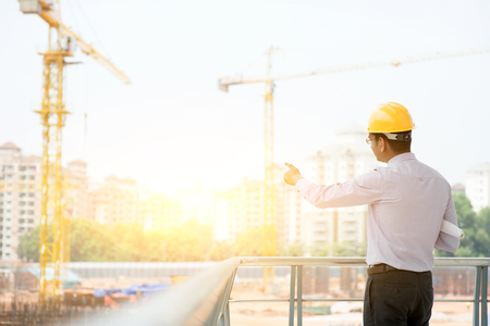 Asian Indian male site contractor engineer with hard hat holding blue print paper pointing at construction site, crane with golden sunlight at the background.