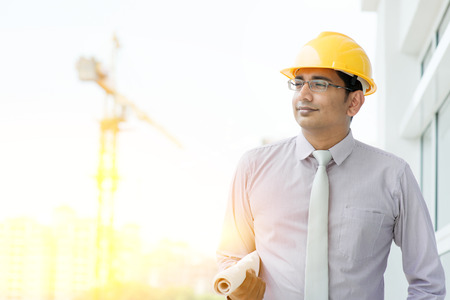 Handsome Asian Indian male site contractor engineer with hard hat holding blue print paper walking at construction site, crane with golden sunlight at the background.