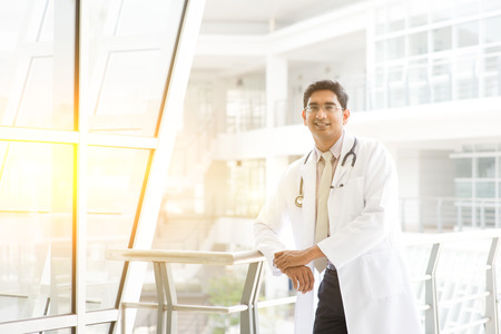 Portrait of confident Asian Indian medical doctor smiling and standing outside hospital building, beautiful golden sunlight at background.