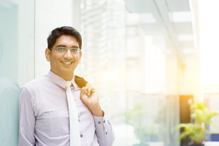 pakistani ethnicity: Portrait of Asian Indian business man smiling, leaning on modern office building block, beautiful golden sunlight at background. Stock Photo
