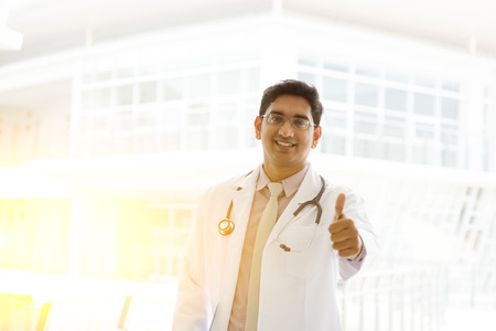 pakistani ethnicity: Portrait of a smiling Asian Indian male medical doctor in uniform thumb up, standing outside hospital building block, beautiful golden sunlight at background.
