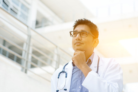 pakistani ethnicity: Portrait of Asian Indian medical doctor thinking and looking away, standing outside hospital building, beautiful golden sunlight at background.
