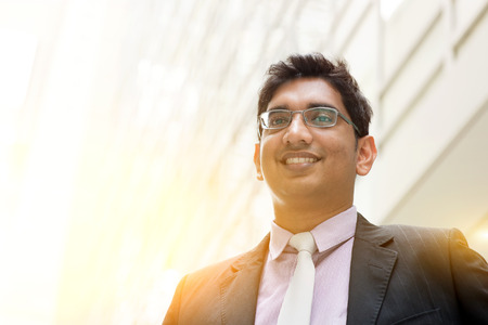 pakistani ethnicity: Portrait of handsome Asian Indian business man smiling, outside modern office building block, beautiful golden sunlight at background.