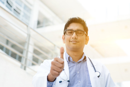 native american man: Portrait of Asian Indian medical doctor smiling and giving thumb up, standing outside hospital building, beautiful golden sunlight at background.